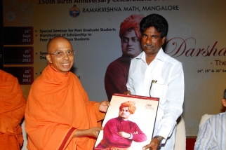 Swami Jitakamananda presenting our token of love to Sri Kota Srinivas Poojari